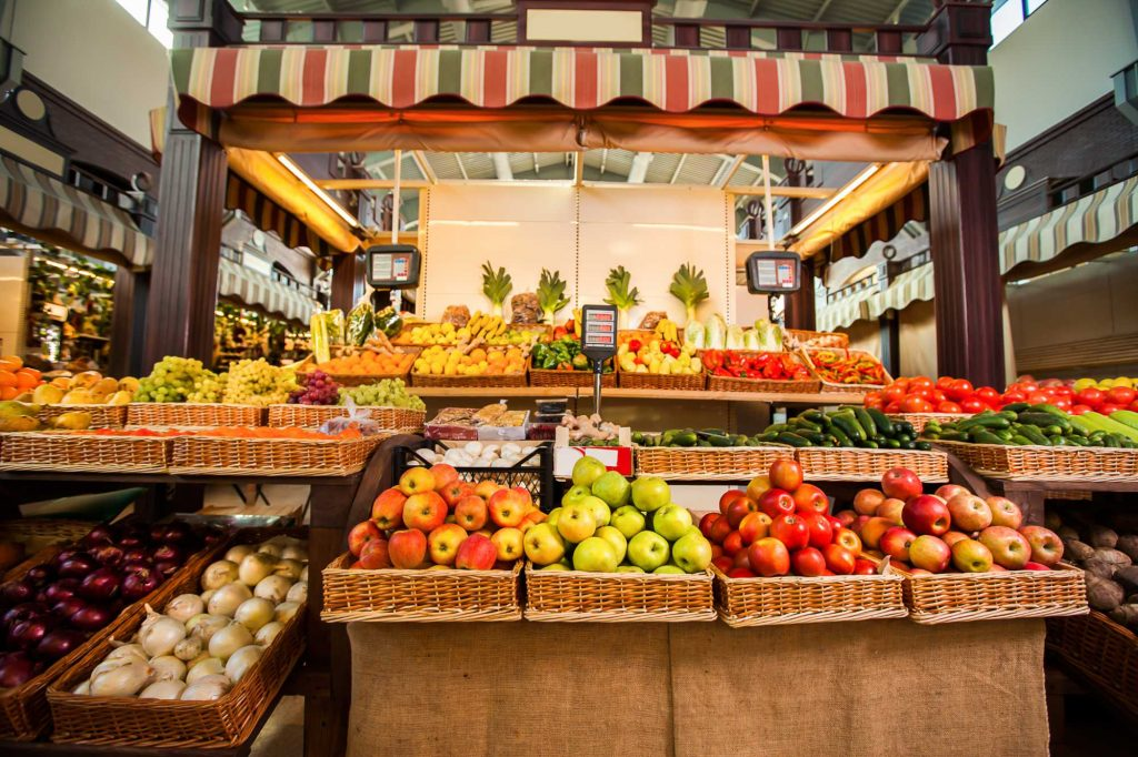 Counters with fresh fruits and vegetables. Greengrocery on the background. Organic food.