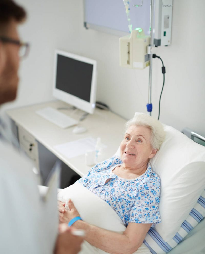 Aged patient lying in bed while talking to her doctor