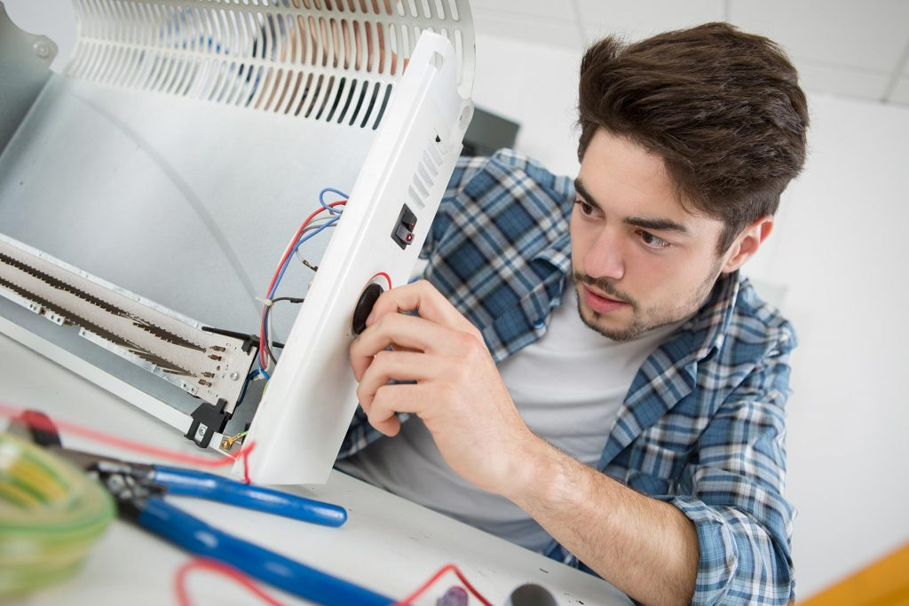 young-male-plumber-examining-electric-heater-PLXD3ZH