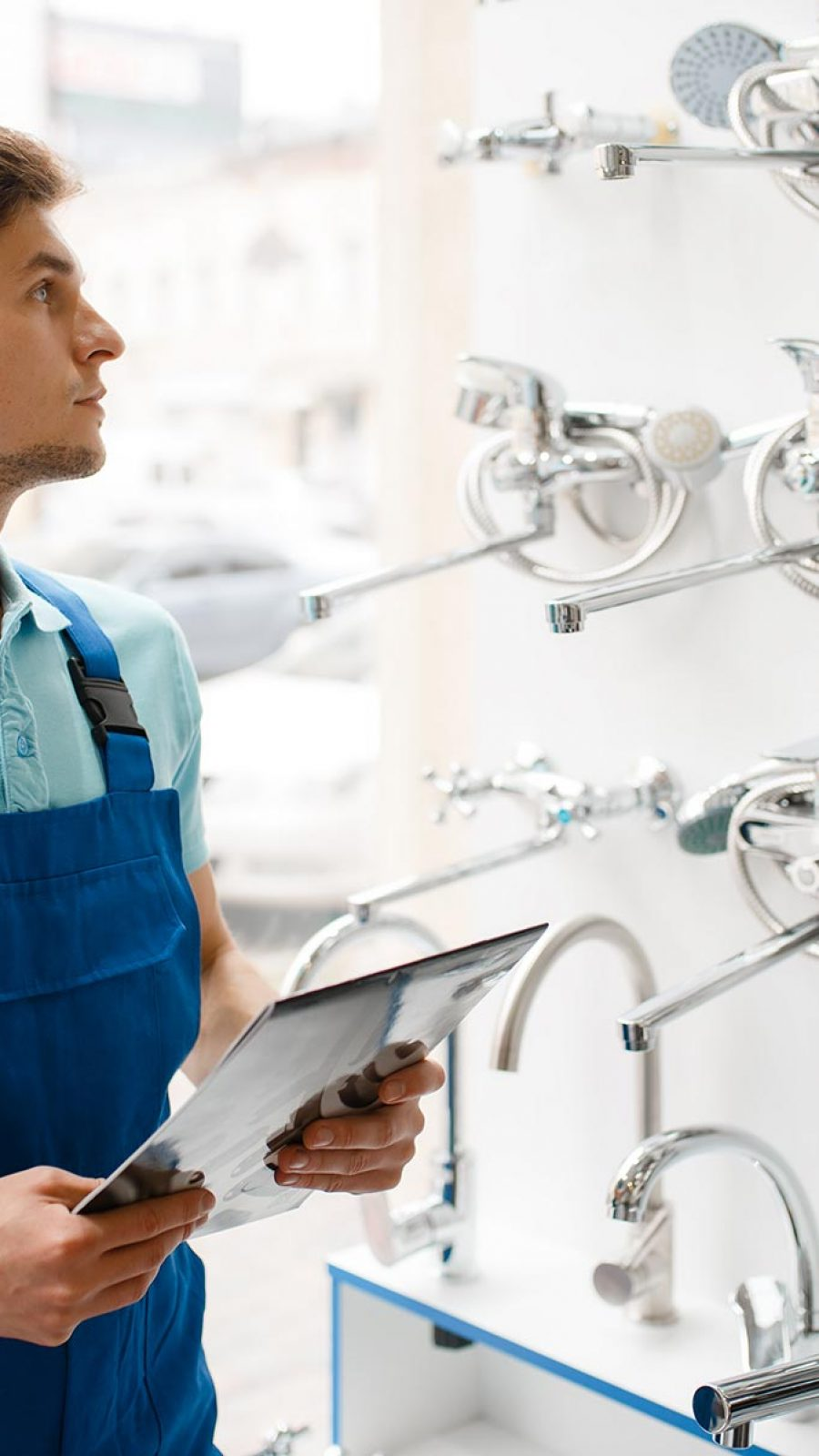 plumber-in-uniform-at-showcase-in-plumbering-store-PLGMWW8