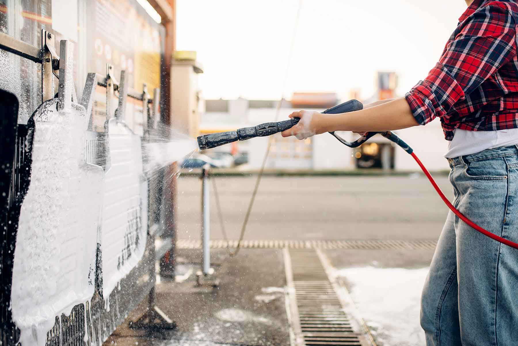 female-person-with-water-gun-cleans-car-mats-URZJMKF