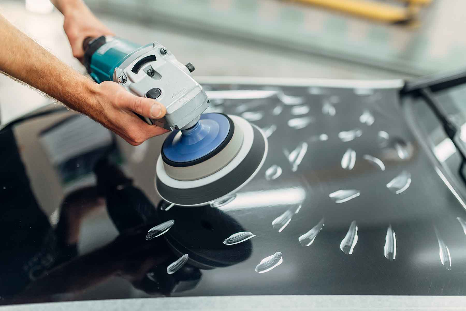 worker-with-polishing-machine-cleans-car-hood-CHRUM83