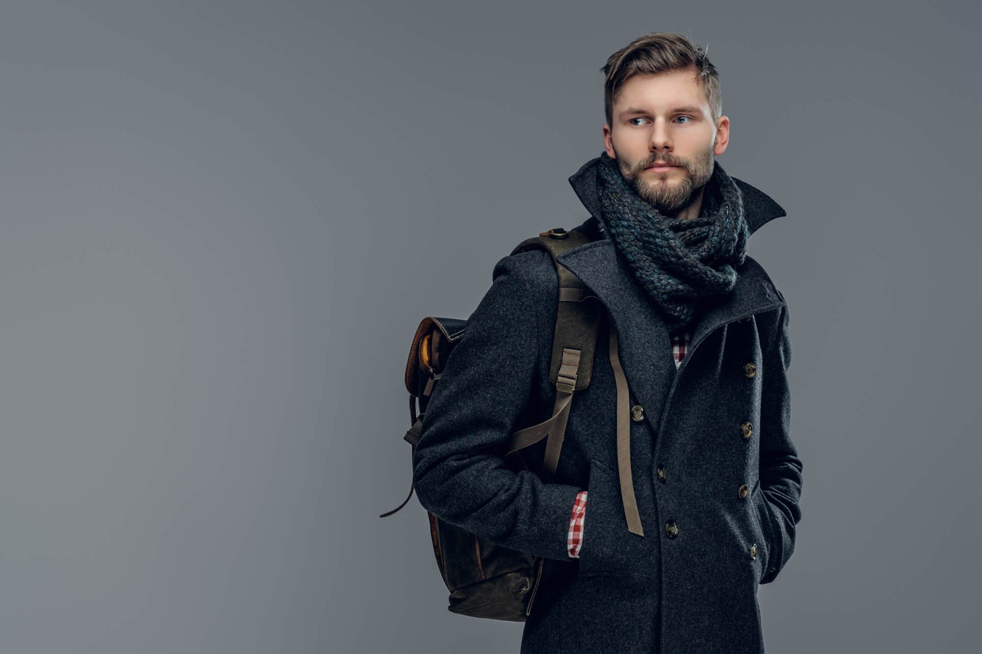 Portrait of bearded male dressed in a warm jacket and a scarf  hold a backpack isolated on grey background.