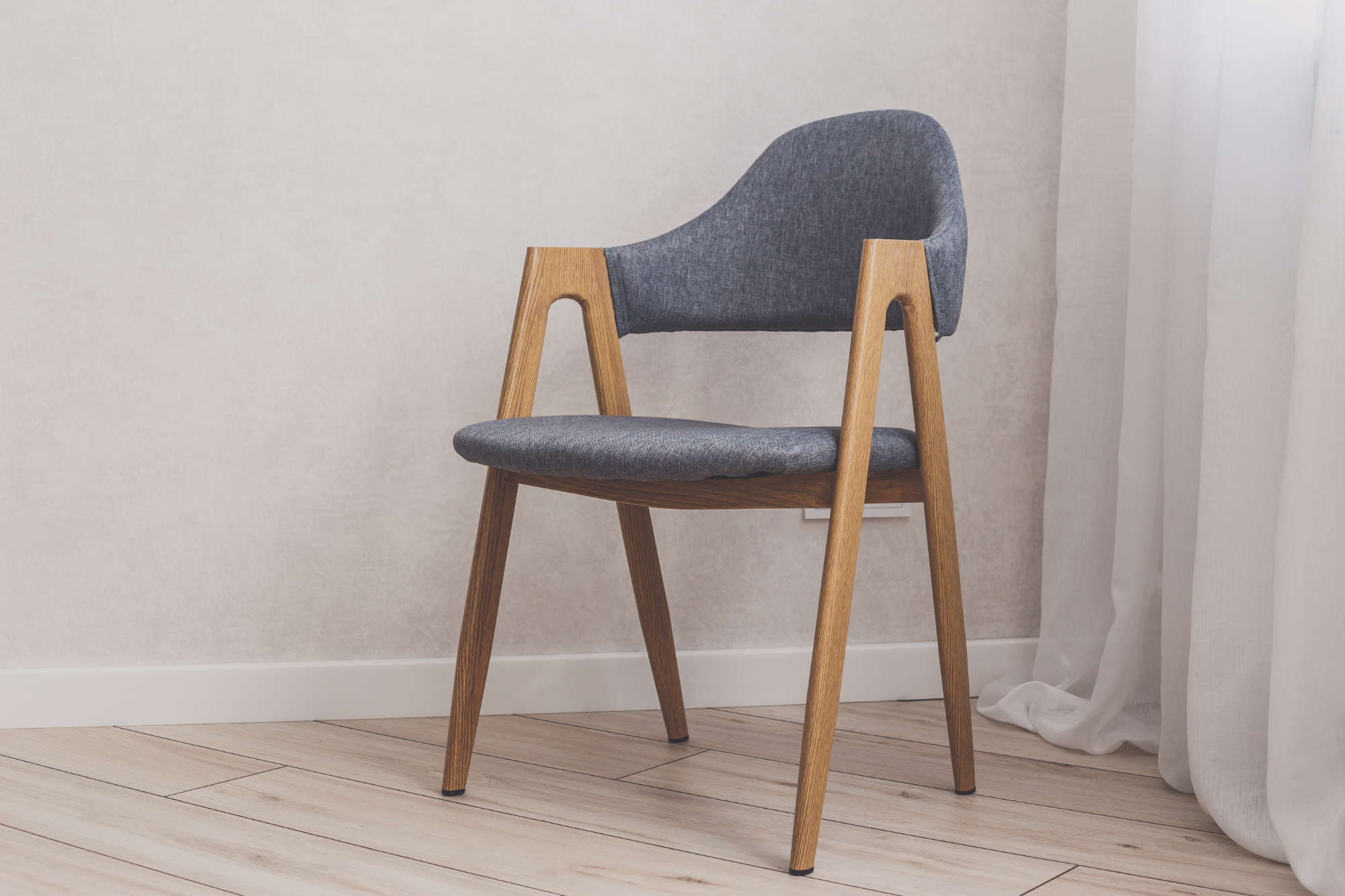 Modern grey chair with white brick walls on background and wood floor.