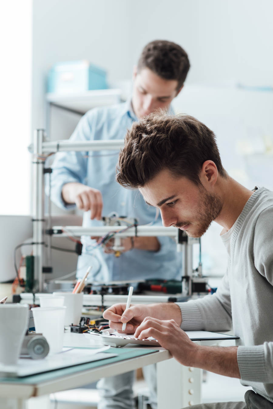 Engineering students working in the lab, a student is using a 3D printer in the background