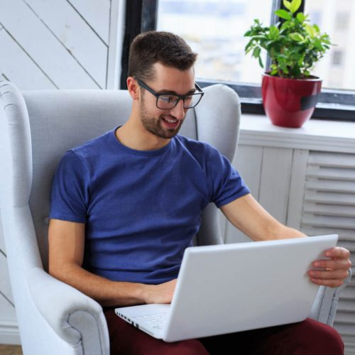 A student sitting on the chair and working with laptop.
