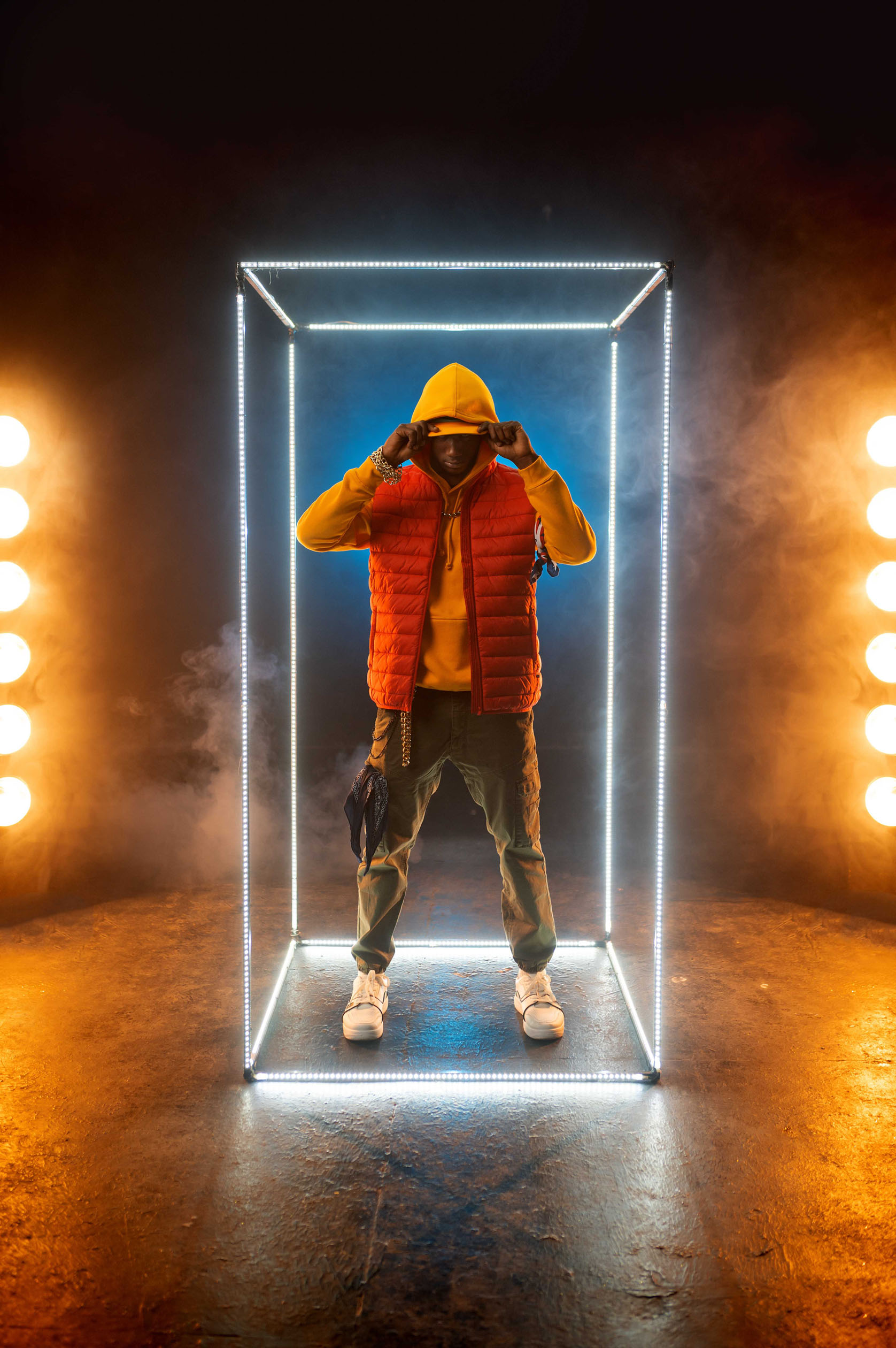 Stylish rapper poses in illuminated cube. Hip-hop performer, rap singer, break-dance performing, entertainment lifestyle