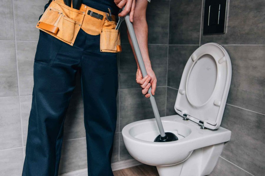 partial-view-of-male-plumber-using-plunger-and-cle-JGX48K8