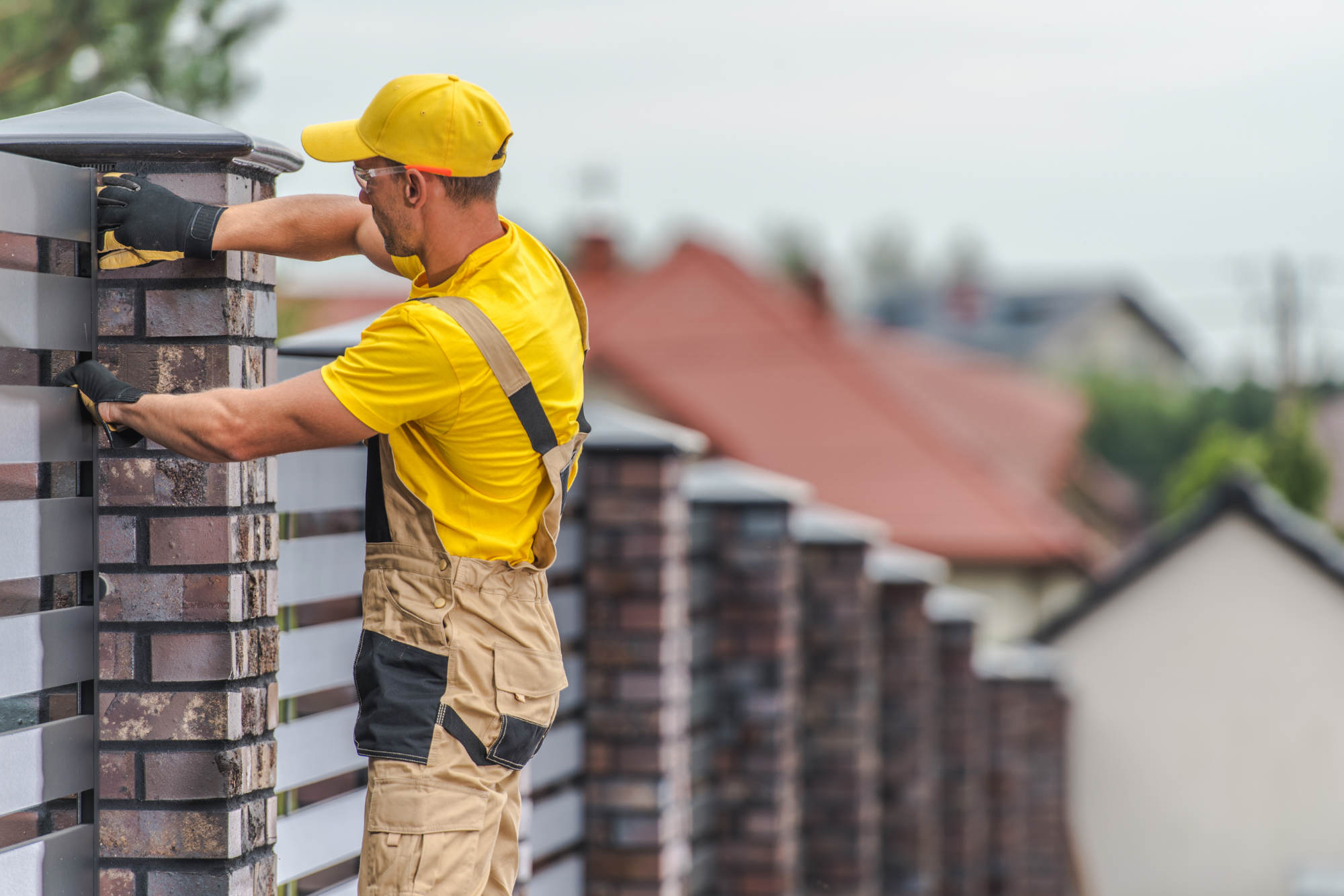 Brick and Wooden Panels Residential Home Fence Building by Professional Caucasian Construction Worker.