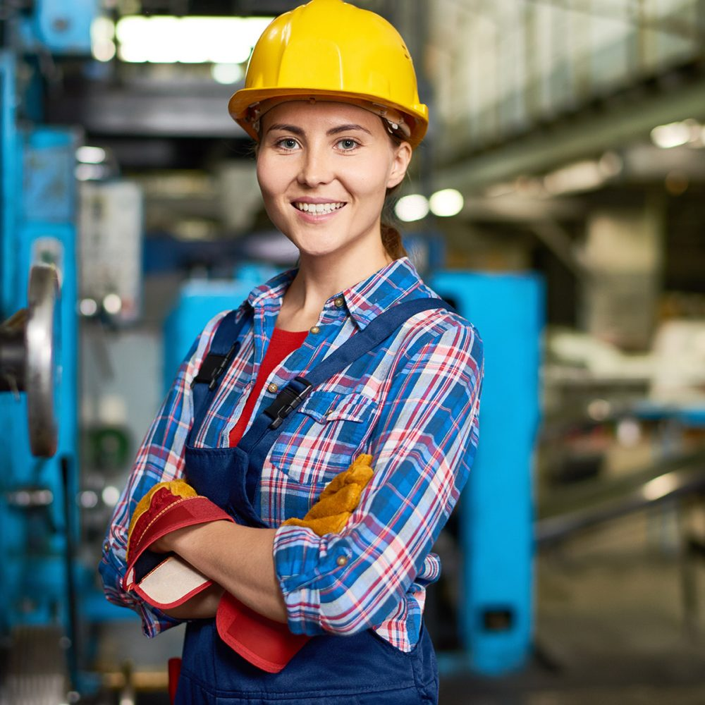 happy-young-woman-working-at-factory-DWN33CH