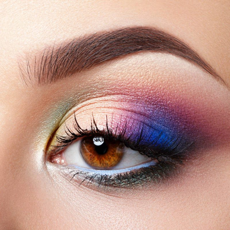 Closeup view of brown female eye with evening makeup. Colourful pink and blue smokey eyes. Studio shot