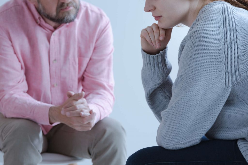Close-up of a young sad woman sharing her grief with a psychotherapy specialist during an individual counseling meeting.