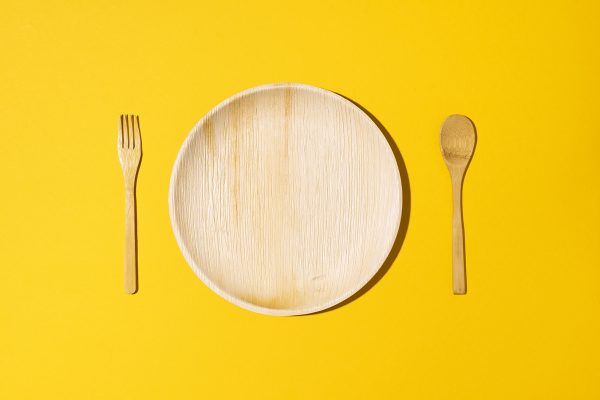 Disposable tableware from natural materials, wooden spoon, fork on yellow background. Eco-friendly sustainable lifestyle. Concept of bamboo, wooden or paper disposable tableware.