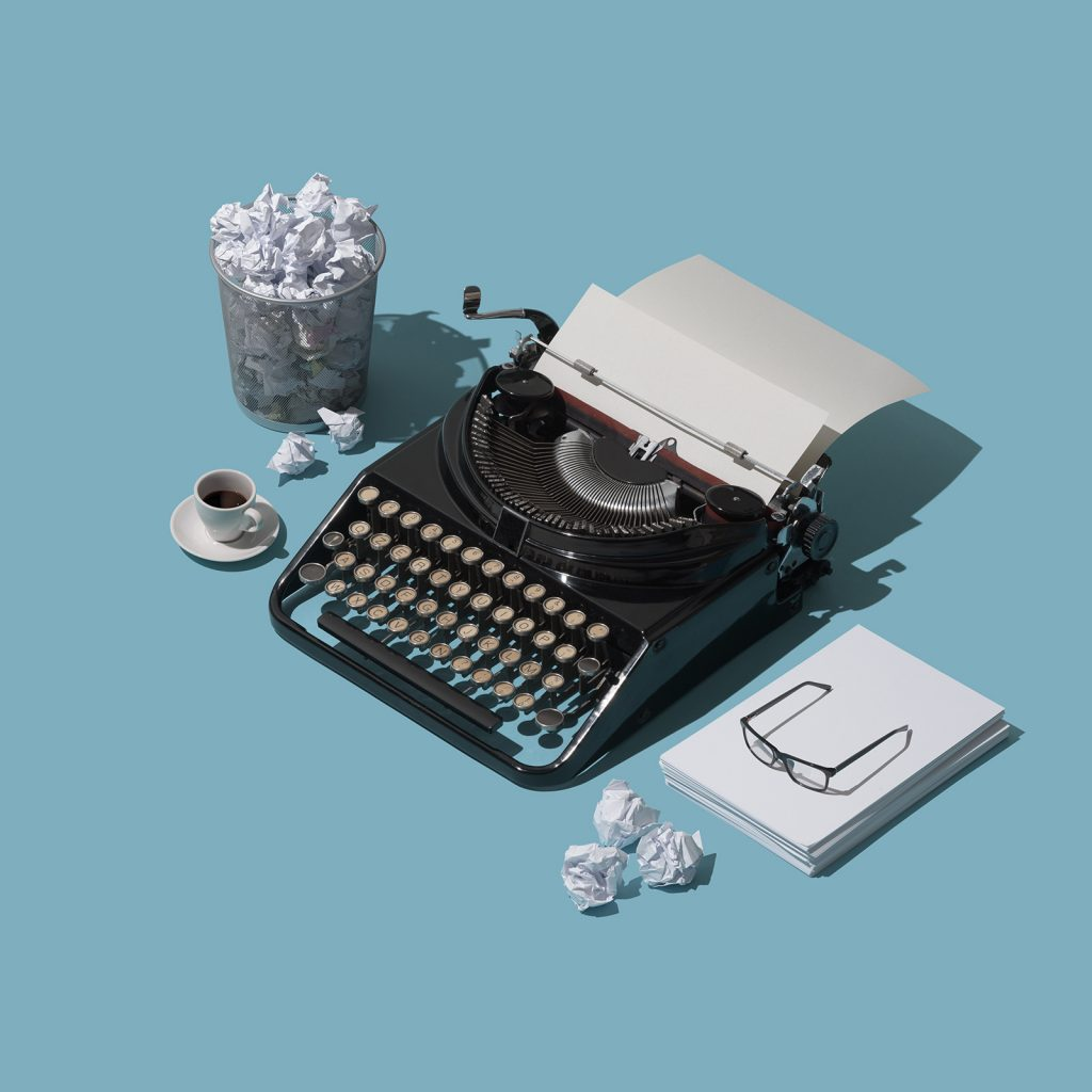 Fear or the blank page and lack of inspiration: vintage typewriter with blank sheet and lots of crumpled paper balls in a trash can