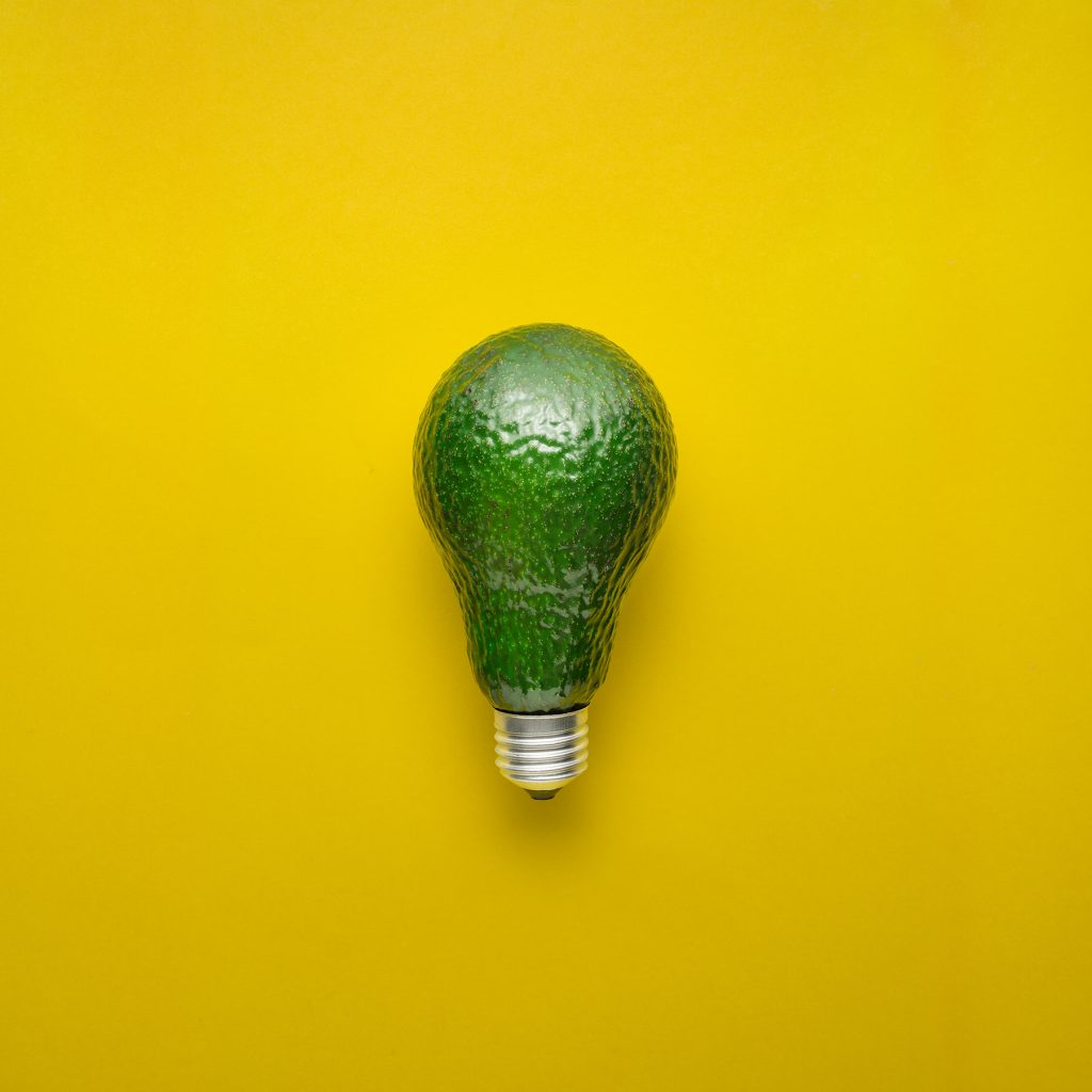 Creative concept photo of avocado as electric bulb on yellow background.