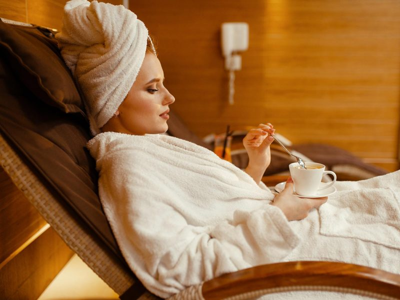 sexy-girl-relaxing-with-cup-of-coffee-in-spa-chair-RG4FKYD