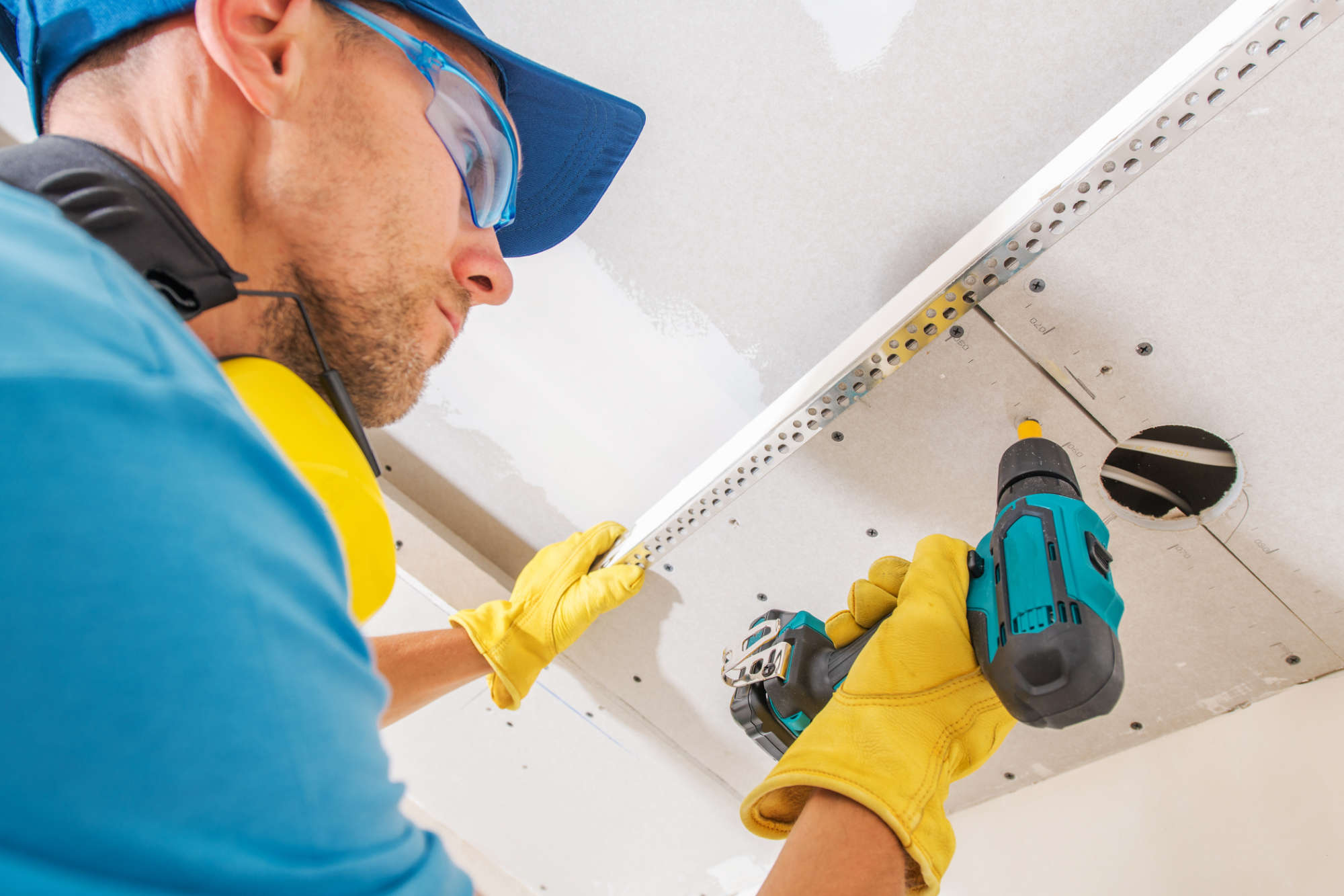 Drywall Ceiling Construction. Caucasian Contractor Worker with Power Tool Building Drywall Elements.