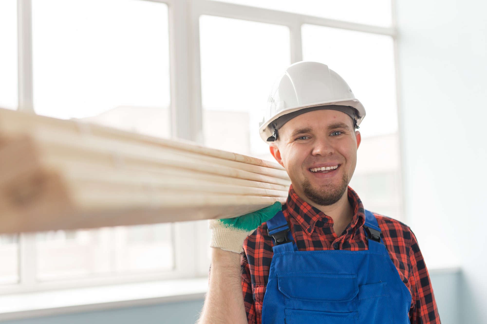 Portrait of handsome white male builder laughing infront of window and wearing white helmet