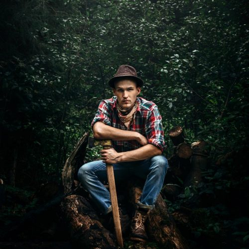 stylish-hipster-lumberjack-with-ax-in-the-sunny-fo-68HK3E8