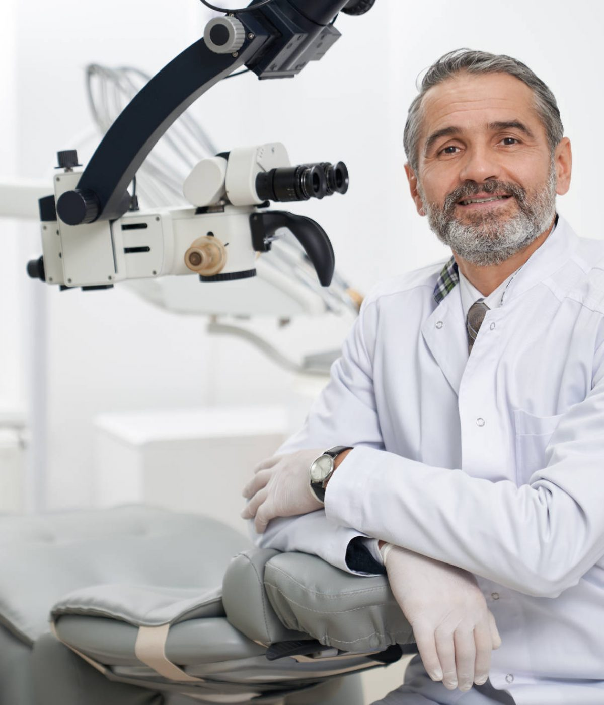 Mature stomatologist posing on workplace, near dental microscope, leaning on dentist chair. Handsome, bearded stomatologist wearing in white medical coat. Man looking at camera and smiling.